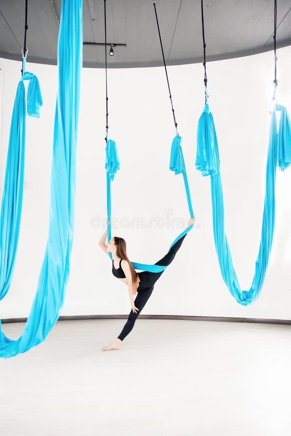 蓝色吊床的年轻美女体操运动员 空中飞行瑜伽在白色演播室 库存照片