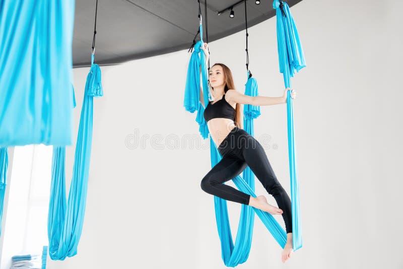 蓝色吊床的年轻美女体操运动员 空中飞行瑜伽在白色演播室 库存图片