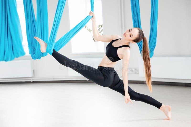 蓝色吊床的年轻美女体操运动员 空中飞行瑜伽在白色演播室 免版税图库摄影