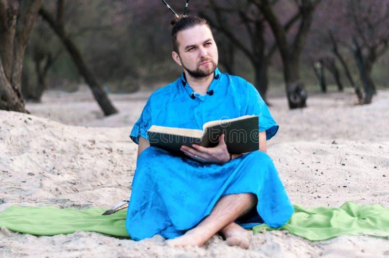 蓝色和服开会的严肃的英俊的有胡子的人,拿着被打开的大书 免版税库存照片