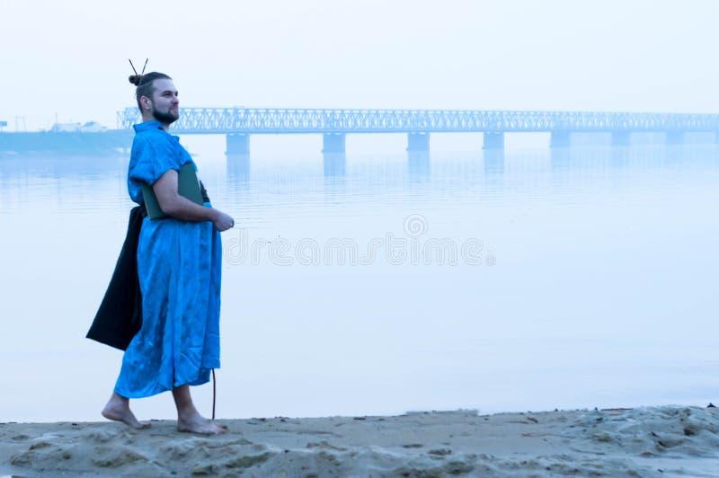 蓝色和服的有胡子的人有在河岸的书的 库存照片