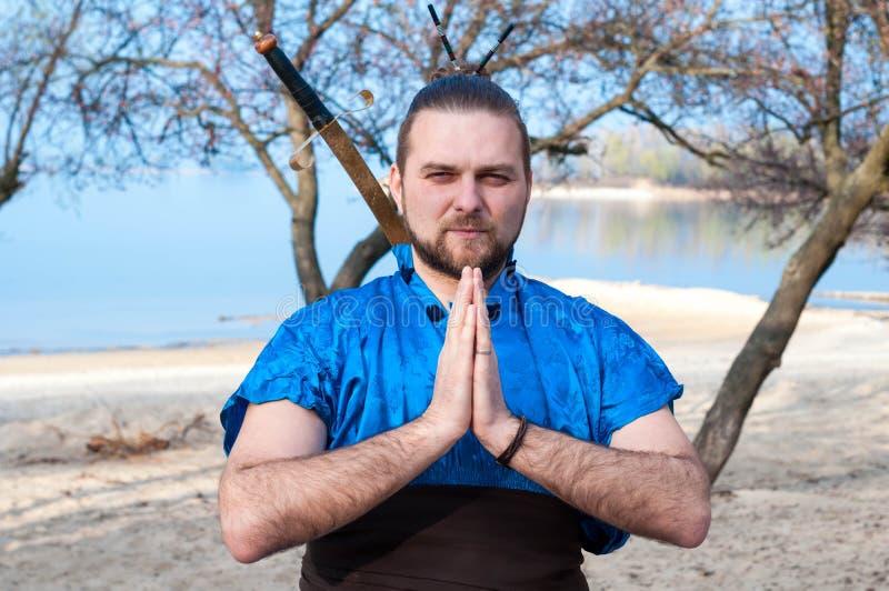 蓝色和服的英俊的严肃的武士,站立用被扣紧的手和剑在后面后 免版税库存图片