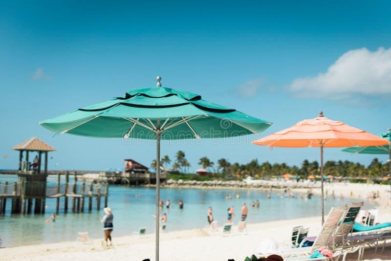 蓝色和橙色伞在清楚的天空下 免版税库存照片