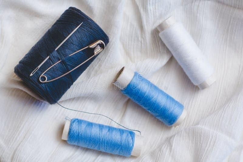 蓝色和白色在白色棉布的螺纹和别针短管轴与缝纫针的 免版税库存照片