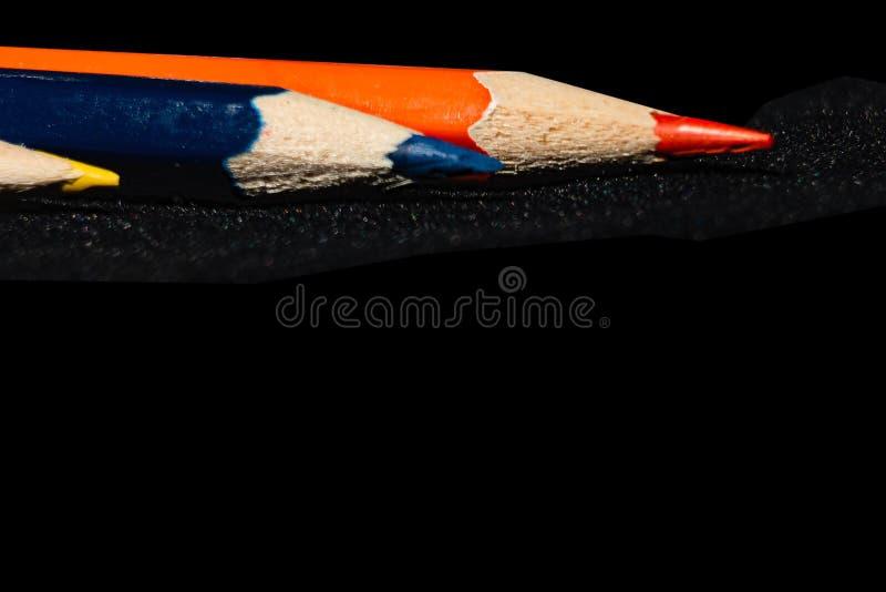 蓝色和黄色和橙色铅笔抽象黑暗的背景  免版税库存照片