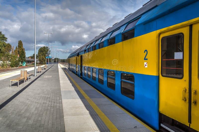 蓝色和黄色火车准备离开在恶劣环境测井半岛驻地的平台 免版税库存照片