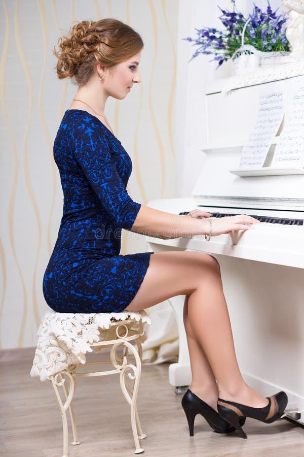 蓝色和黑礼服的性感的妇女 免版税库存照片