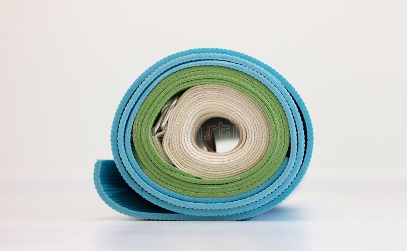 蓝色和绿色瑜伽一起被扭转的席子和白色皮带 库存图片