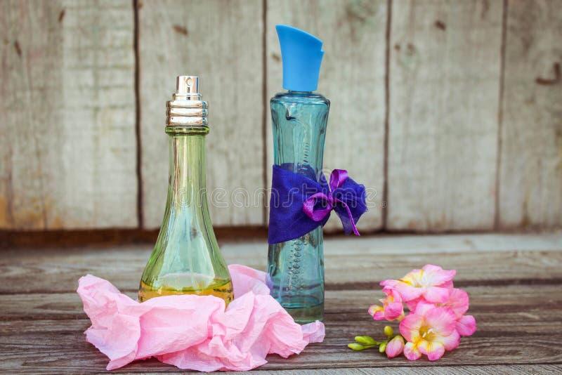 蓝色和绿色香水瓶临近花fresia 图库摄影
