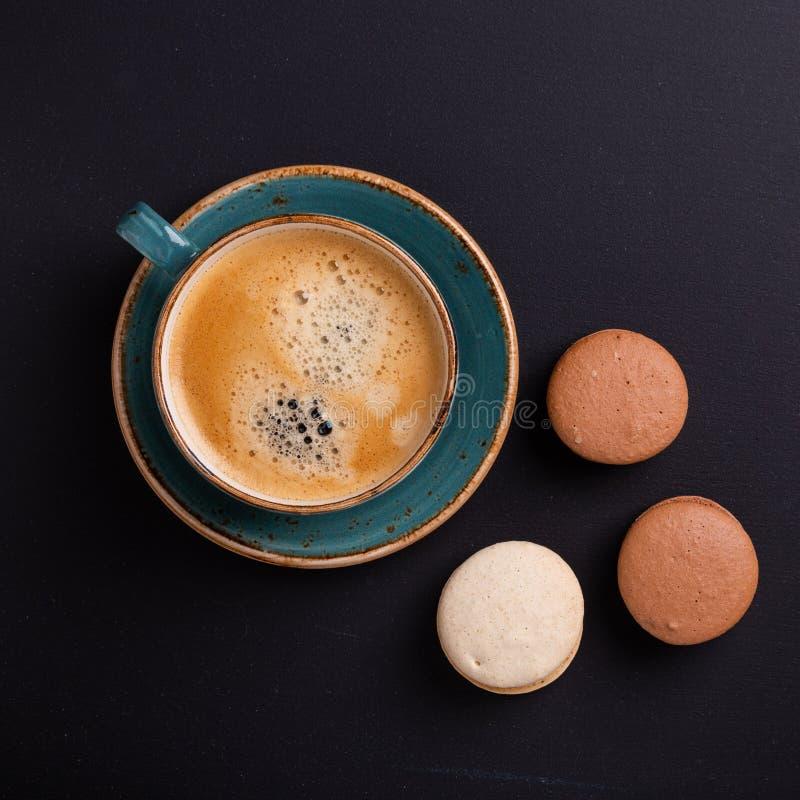 蓝色咖啡和蛋白杏仁饼干在黑暗的木桌上 Coffe中断 图库摄影