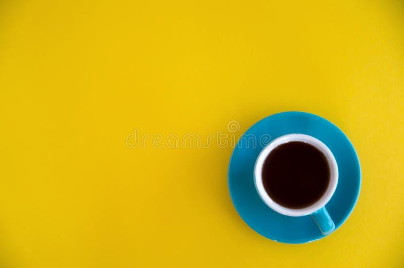 蓝色咖啡在黄色背景的立场 早晨早餐,事务 库存图片