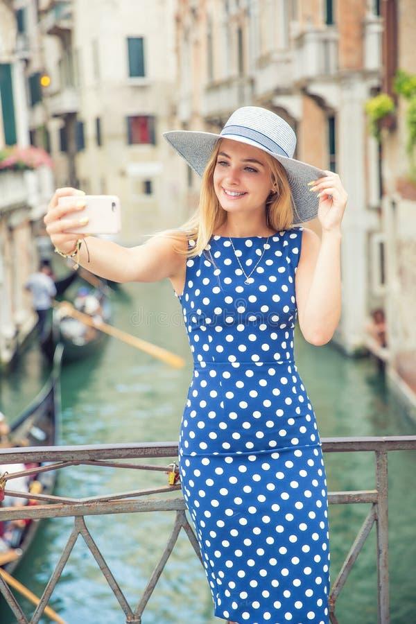 蓝色圆点礼服的美丽的gir旅客游人在威尼斯意大利做selfie 可爱的白肤金发的时装模特儿年轻女人 免版税库存照片
