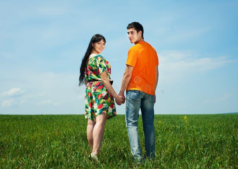 蓝色在天空的夫妇愉快的草甸 库存照片