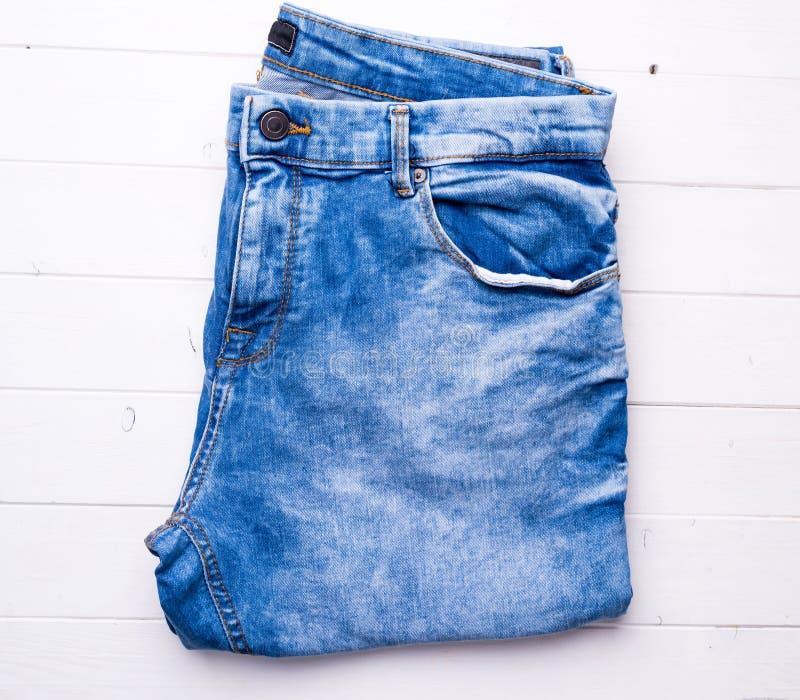 蓝色在木背景的被折叠的牛仔裤 图库摄影