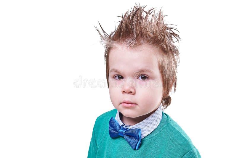 蓝色在白色背景隔绝的蝶形领结和绿色毛线衣的英俊的小男孩 免版税库存照片