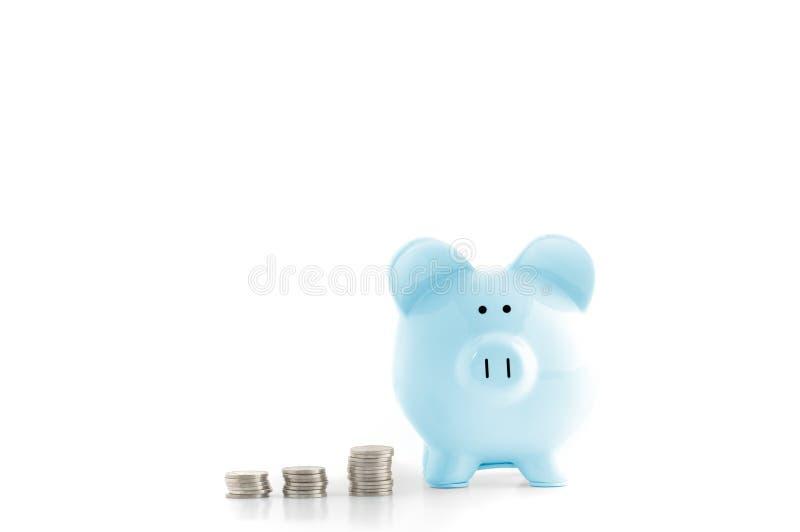 蓝色在白色隔绝的存钱罐和硬币 免版税库存照片