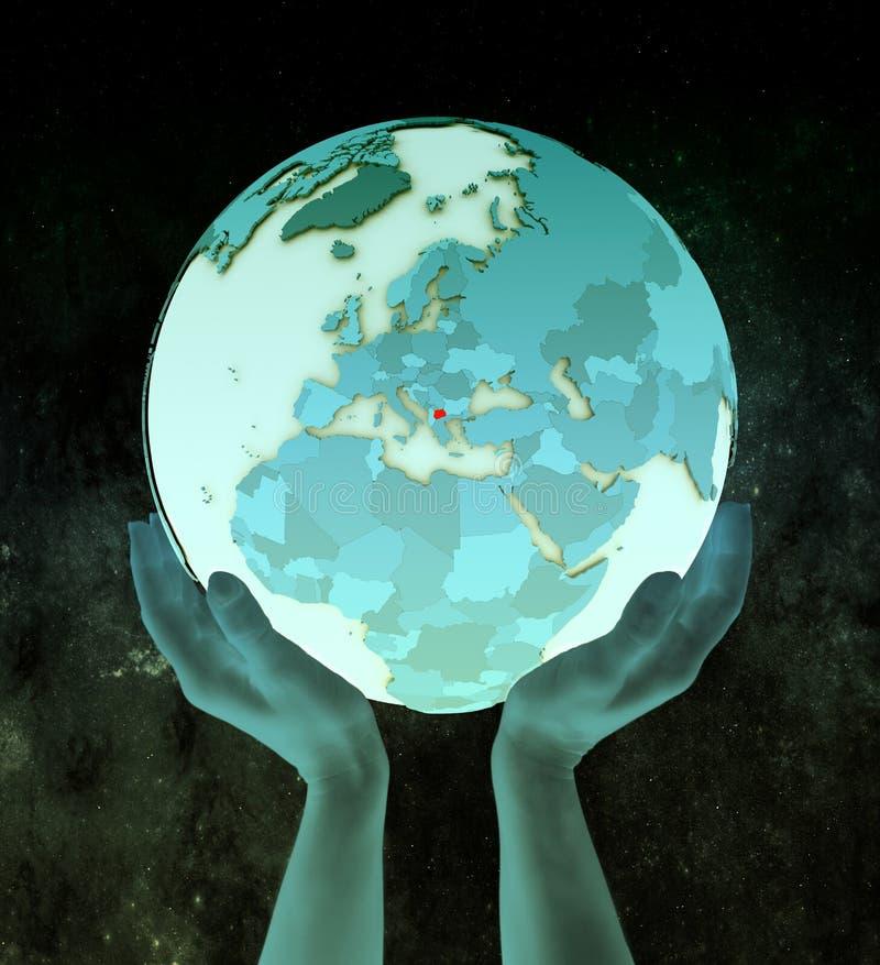 蓝色地球的马其顿在手上 库存照片