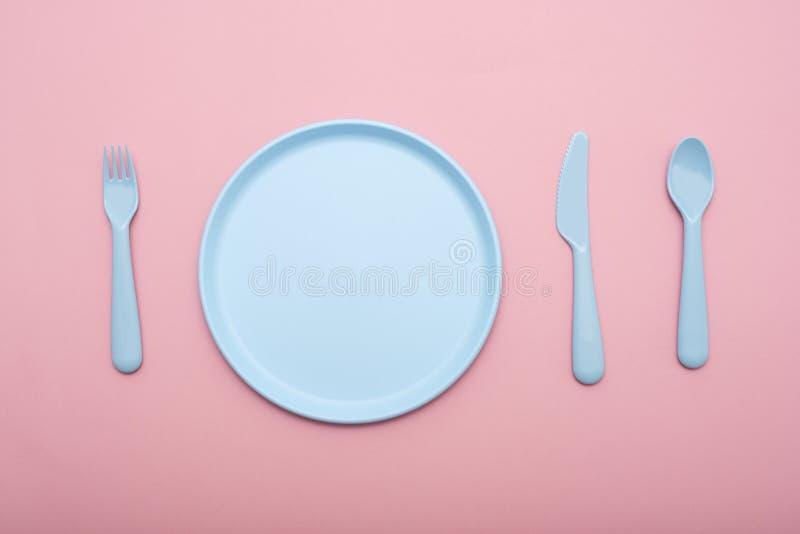 蓝色塑料碗筷:板材、叉子、刀子和匙子在桃红色背景 免版税库存图片