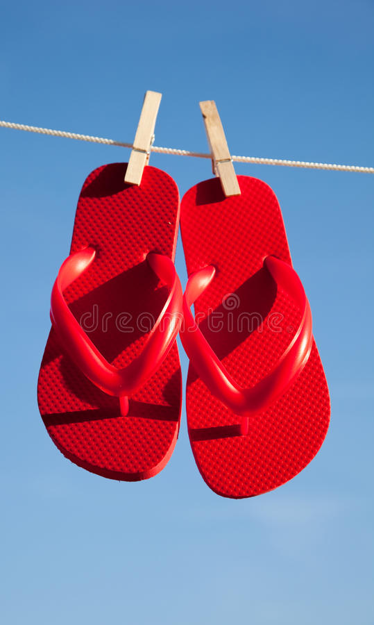 蓝色塑胶人字平底拖鞋对红色天空 库存照片