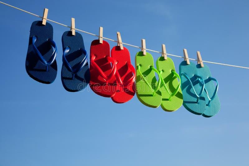 蓝色塑胶人字平底拖鞋荡桨天空 免版税图库摄影