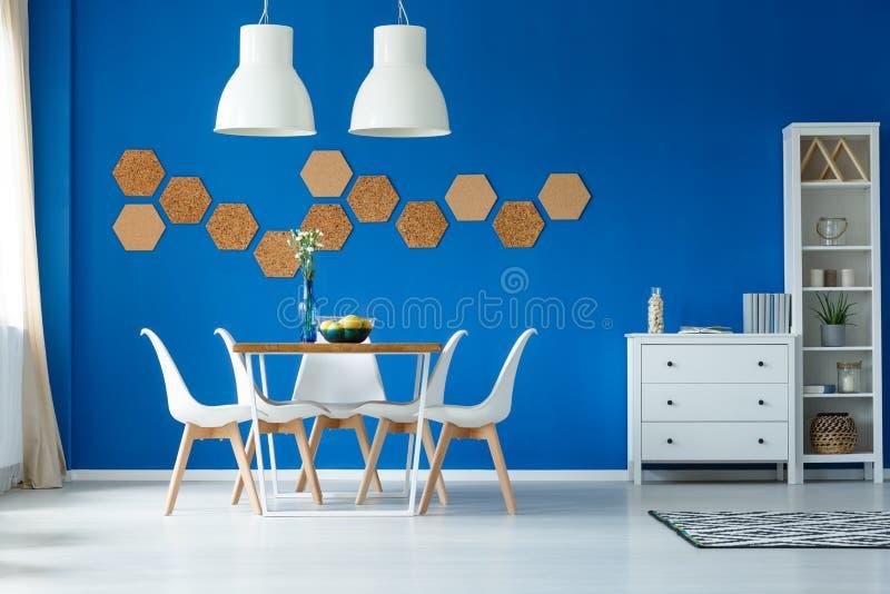 蓝色墙壁和简单的家具 免版税库存照片