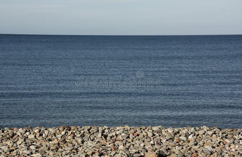 蓝色天际作为pebbled海滩和看集会天空 免版税库存图片