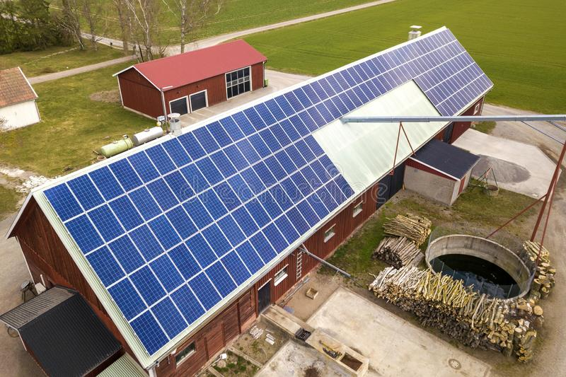 蓝色太阳在木大厦、谷仓或者房子屋顶的照片流电盘区系统顶视图  可更新的生态绿色能量 免版税库存图片