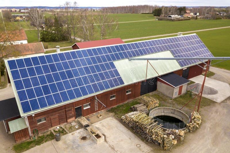 蓝色太阳在木大厦、谷仓或者房子屋顶的照片流电盘区系统顶视图  可更新的生态绿色能量 库存图片