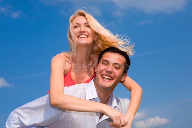 蓝色夫妇爱微笑在年轻人之下的天空 图库摄影