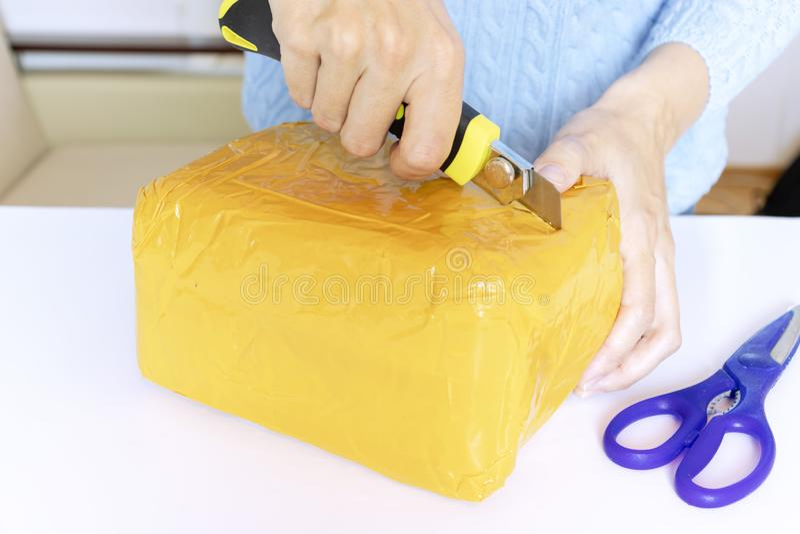 蓝色套头衫的一名妇女打开,箱中取出与剪刀和刀子的橙色小包 免版税库存照片
