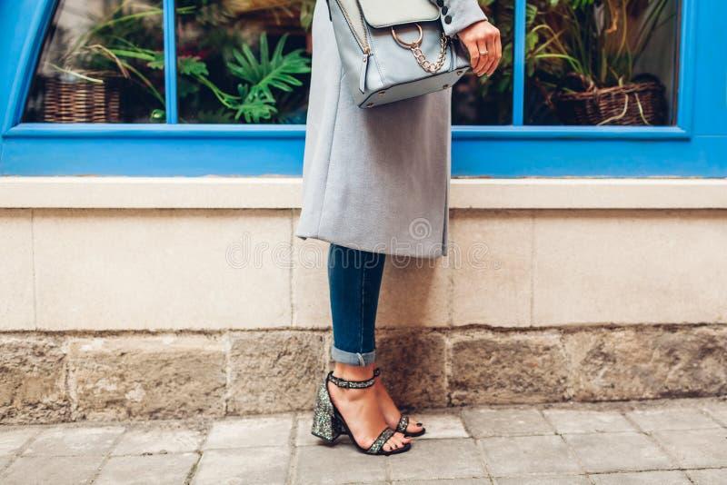 蓝色女性提包和鞋子特写镜头  拿着皮包的妇女户外 时髦的衣物和辅助部件 免版税图库摄影