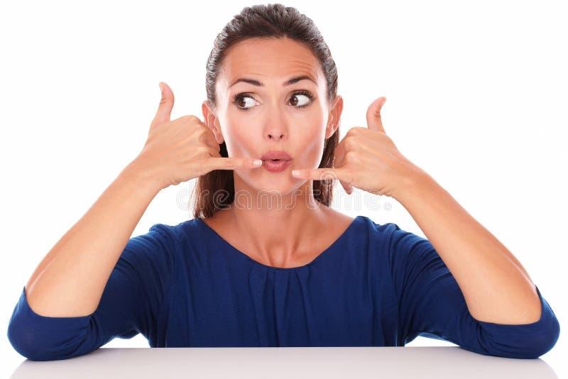 蓝色女衬衫的女孩打手势电话的 免版税图库摄影