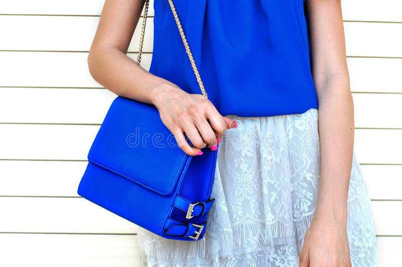 蓝色女衬衫的时髦妇女和白色鞋带避开拿着小蓝色皮包w 图库摄影