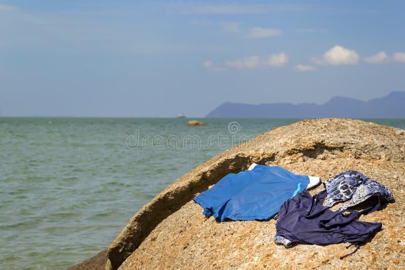 蓝色妇女的泳装和蓝色人的游泳裤干燥在石头反对风平浪静的背景和与云彩的天空 免版税库存图片