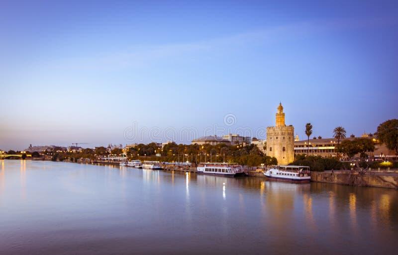 蓝色小时观点的金黄塔或Torre沿瓜达尔基维尔河河的del Oro,塞维利亚,西班牙 免版税库存照片