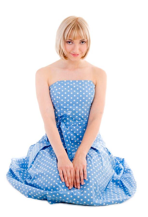 蓝色小点礼服短上衣坐的妇女 图库摄影