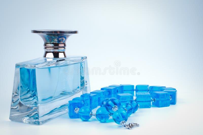 蓝色小珠和瓶香水 库存照片