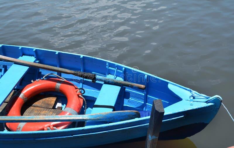 蓝色小船停泊了在风平浪静的码头 免版税库存图片