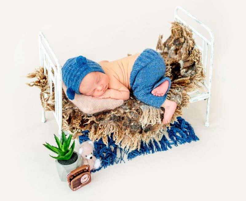 蓝色帽子睡觉的逗人喜爱的男孩 库存照片