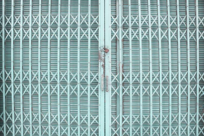 蓝色或绿色滚动的钢门或路辗快门门交织背景和生锈锁着的样式 库存照片