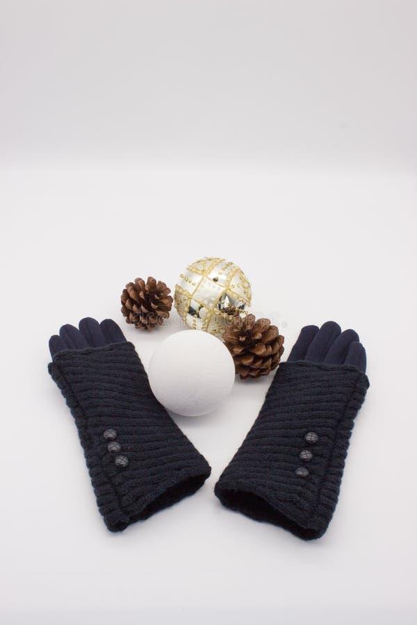 蓝色手套、白色和金黄圣诞节球和两个杉木锥体在白色背景 新的Year's和圣诞节概念 免版税库存图片