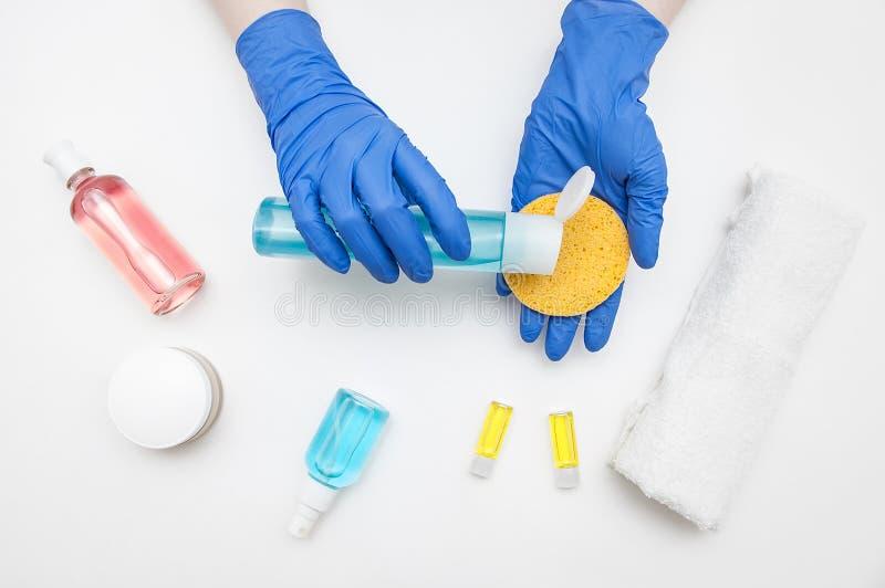 蓝色手套的一位美容师医生拿着有化妆水的一个蓝色瓶和面孔的一块黄色海绵在白色背景 免版税库存图片