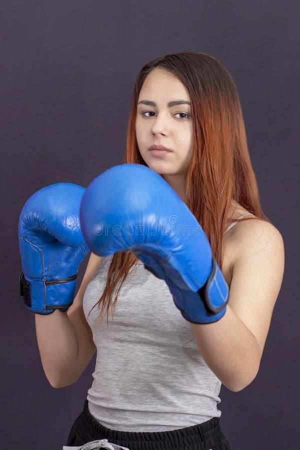 蓝色拳击手套的拳击手女孩在机架的一件灰色T恤杉 免版税库存照片