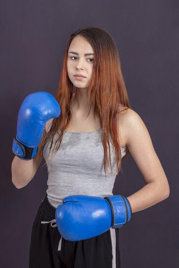 蓝色拳击手套的拳击手女孩在机架的一件灰色T恤杉 库存照片