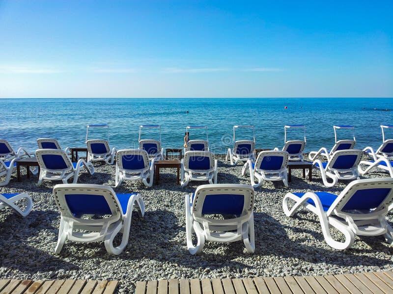 蓝色支架床在Pebble海滩站立,反对蓝色海 免版税库存图片