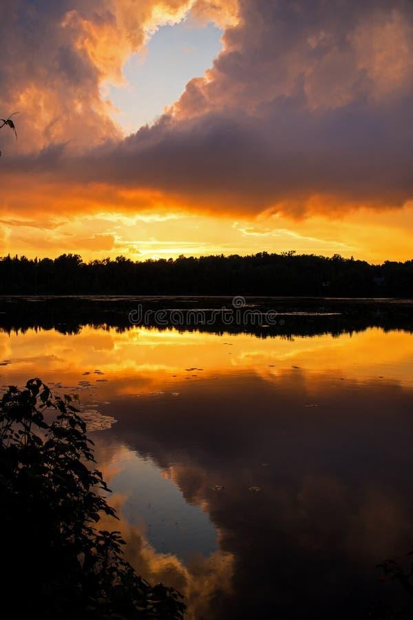 蓝色断裂通过五颜六色的日落云彩 免版税库存照片