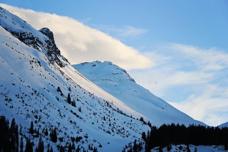 蓝色斯诺伊山边在冬天阿尔卑斯的莱赫滑雪场 免版税库存图片