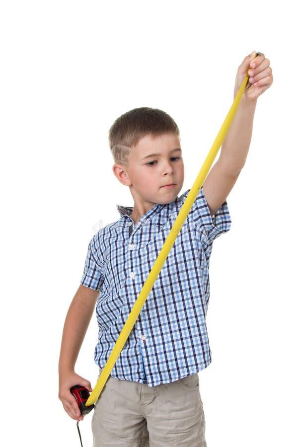 蓝色方格的衬衣的逗人喜爱的少年男孩,有在白色的一卷测量的磁带的隔绝了背景,修建概念 免版税图库摄影