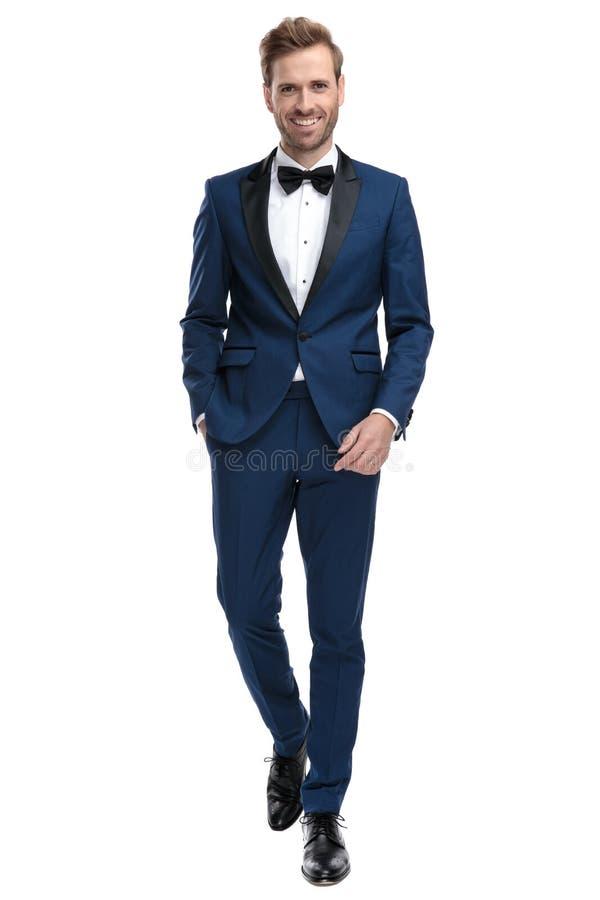 蓝色无尾礼服的愉快的人走用在口袋的手的 免版税图库摄影