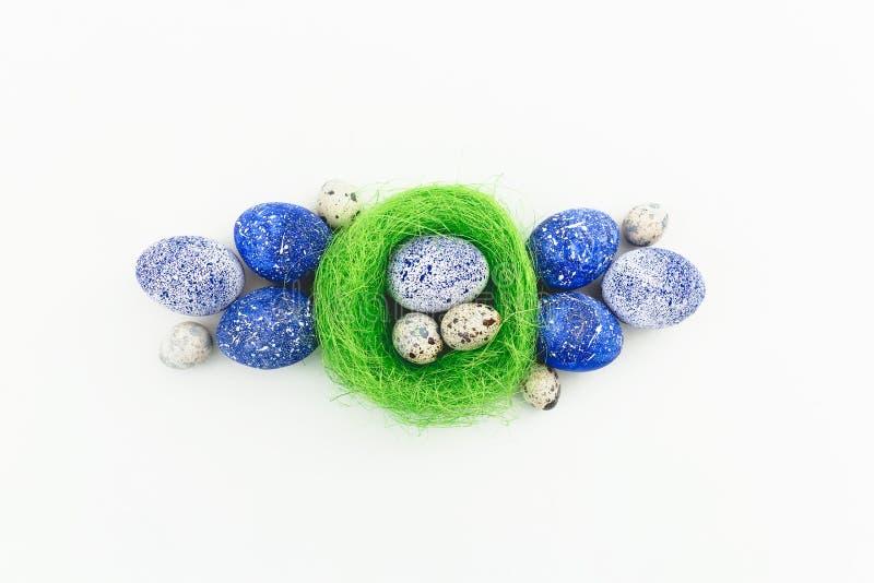 蓝色有斑点的复活节彩蛋和鹌鹑蛋在巢在白色背景 平的位置,顶视图 愉快的复活节 免版税库存照片